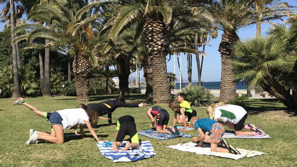 Triathlon kids doing functional training under some palm trees