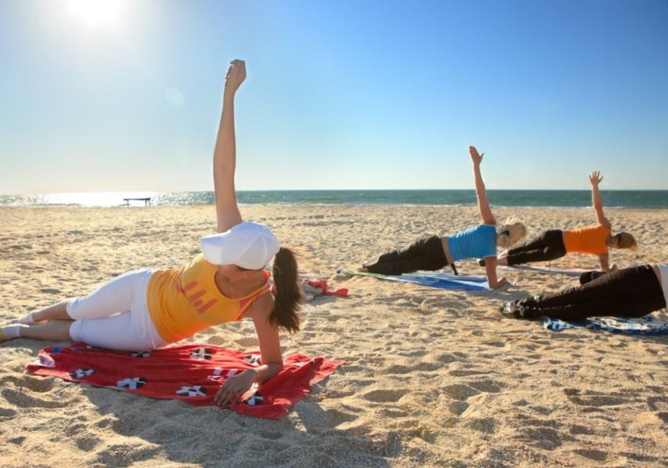 Athletes practising yoga on the beach