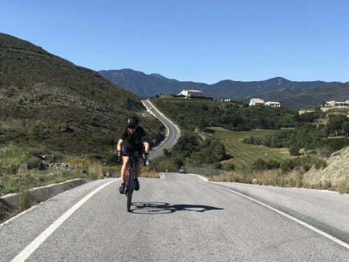 Female cyclist climbing a hill in Marbella